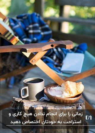 صندلی استراحت چوبی در کنار یک لیوان و چای و شیرینی برای استراحت