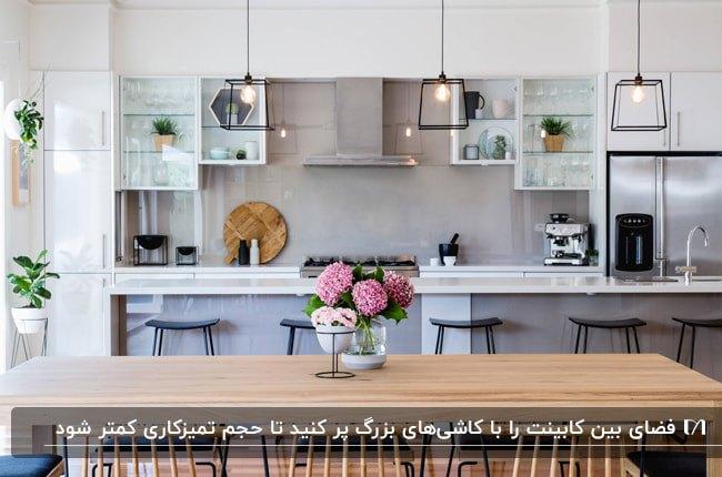 آشپزخانه ای با کابینت های سفید و طوسی و قفسه های باز اطراف هود