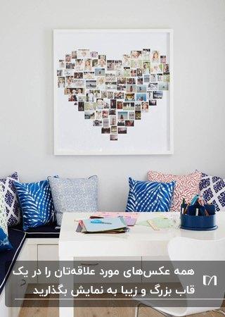 گوشه ای دنج برای نشستن با نیمکت ال شکل و کوسن های آبی و صورتی و یک تابلوی قلب با عکس های چاپی