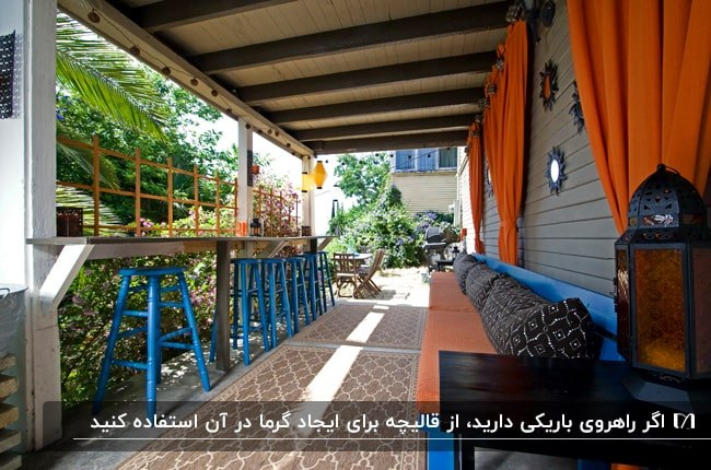 ایوان باریک و بلندی با نیمکت آبی و نارنجی با کوسن های قهوه ای و یک قالیچه باریک وسط راهرو