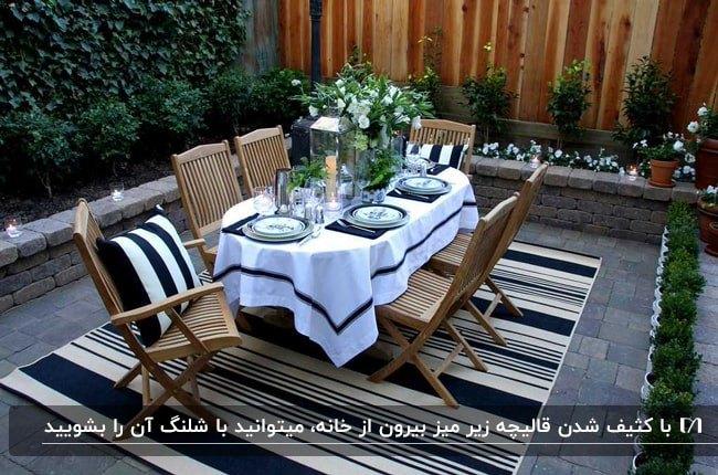 تصویر میزغذاخوری چوبی شش نفره در فضای باز خانه با فرش راه راه سفید و مشکی