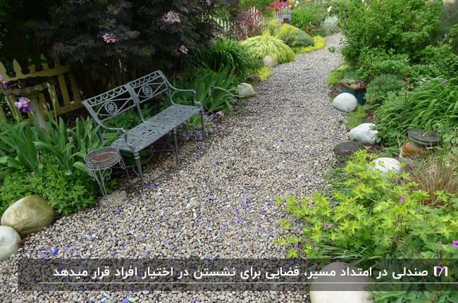نیمکتی فلزی در مسیر پیاده روی سنگی در باغ خانه