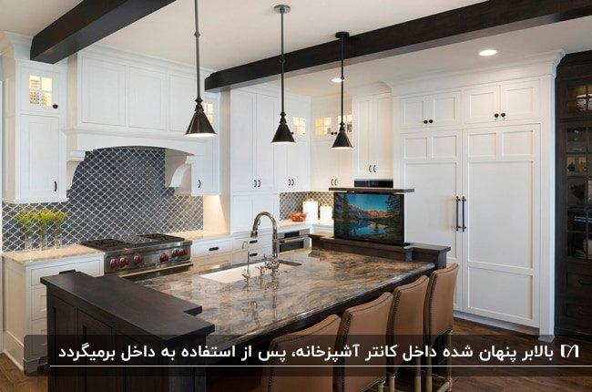 آشپزخانه ای با کابینت های سفید و جزیره چوبی به همراه یک تلویزیون کشویی مخفی داخل جزیره