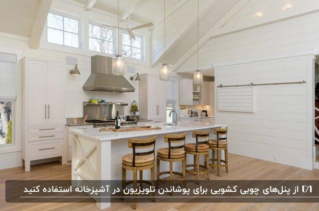 آشپزخانه ای به سبک انبار با کابینت های سفید و تلویزیون روی دیوار و درب کشویی برای مخفی کردنش