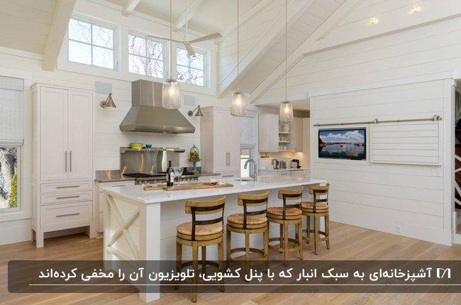آشپزخانه با کابینت های سفید چهارپایه های چوبی جزیره و تلویزیون مخفی با درب کشویی روی دیوار