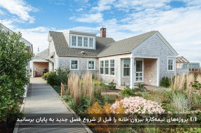 خانه ای با به رنگ طوسی با پنجره های سفید و کفپوش چوبی برای مسیر جلوی ویلا