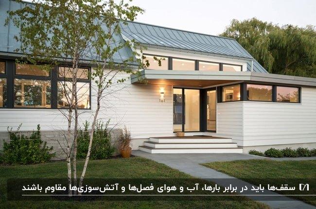 تصویر خانه ای با نمای سفید و درب شیشه ای به همراه سقف شیروانی شیب دار