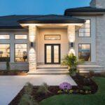 تصویری از نمای خارجی سفید یک خانه با حیاط محوطه سازی شده