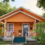 تصویری از نمای خارجی نارنجی رنگ یک خانه با درب و پله های آبی تیره
