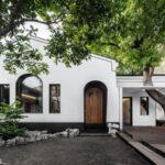 محوطه ورودی خانه ای با ترکیب رنگ های سفید و مشکی و درب های نیم دایره ای