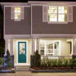 تصویر ورودی یک خانه طوسی رنگ با پنجره های سفید و درب ورودی سبزآبی