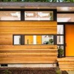 تصویر خانه ای با نمای چوبی به پلاک 1603 و درب ورودی نارنجی