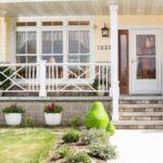 تصویری از نرده های سفید ورودی یک خانه با نمای خارجی نخودی رنگ