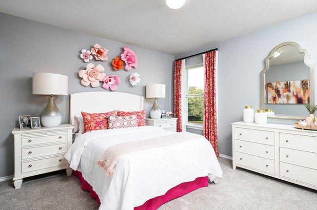 تخت خواب دو نفره با پتوی سفید و صورتی با گل های بزرگ دیواری