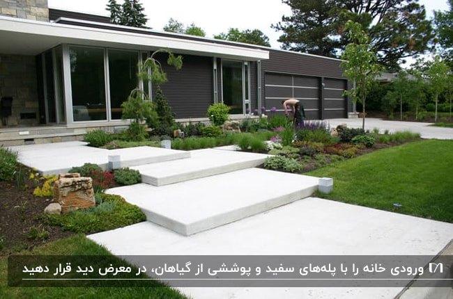 ورودی خانه ای با نمای قهوه ای و پله های بزرگ سفید با گل ها و گیاهان اطرافش