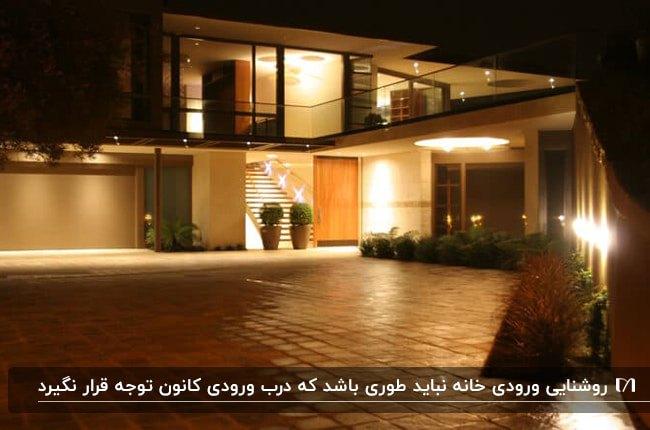 نمای خارجی نورپردازی شده خانه ای با درب چوبی و پنجره های شیشه ای
