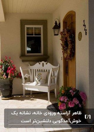ورودی زیبای خانه ای با درب چوبی، نیمکت کلاسیک سفید و گلدان های گل