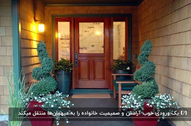 وروردی چوبی خانه ای با نیمکت چوبی میان باکس های گل دو طرف درب