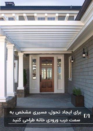 ورودی خانه ای با ستون های سفید و درب قهوه ای بادیوارهای خاکستری