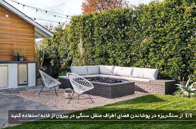 استفاده از سنگ ریزه برای پوشاندن فضای اطراف یک منقل سنگی در بیرون از خانه