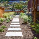 تصویر حیاطی با باغچه های دو طرف مسیر