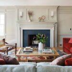 شومینه بتنی خاکستری روی دیوار سفید و با مبل طوسی و قرمز