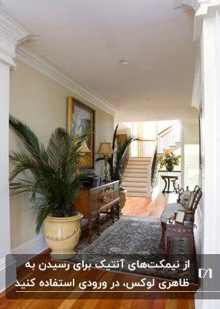 ورودی داخلی خانه ای با نیمکت آنتیک مقابل کنسول چوبی و گلدان های گل بزرگ دو طرف کنسول