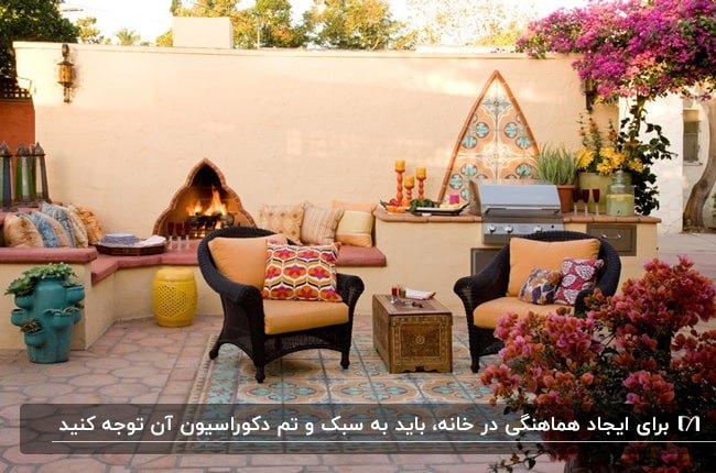 پاسیویی مراکشی با مبلمان حصیری و پارچه نارنجی، نیمکت های سیمانی و گل های سرخابی