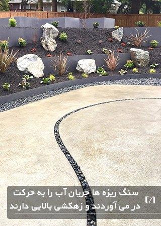تصویری از یک پاسیو بتنی، که یک فضای باریک در راستای باغچه آن با سنگ ریزه پر شده است