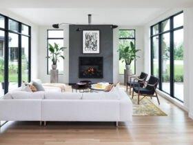 نشیمنی با دیوارهای شیشه ای، مبل سفید و دو صندلی مشکی و دیوار خاکستری شومینه