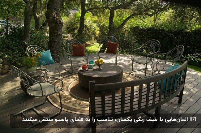 فضای بازی با صندلی های فلزی به همراه کوسن های آبی و قرمز، نیمکت چوبی و میز عسلی گرد