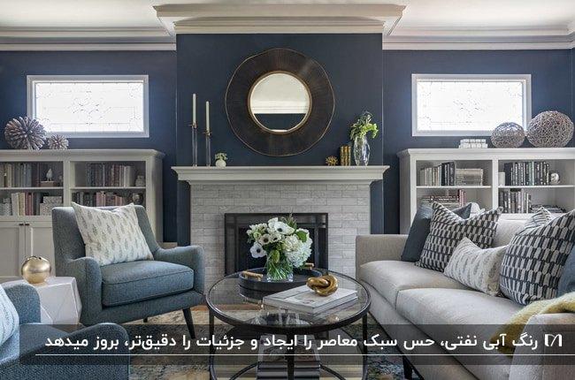 نشیمنی با دیوارهای آبی نفتی، مبلمان طوسی و خاکستری، شومینه و آینه گرد بالای آن