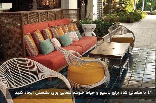 تصویر پاسیویی با مبل نارنجی به همراه کوسن های رنگی و صندلی های سفید با پارچه طلایی