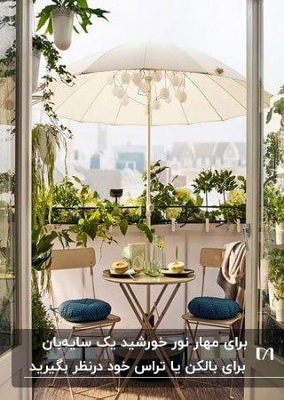 بالکنی با سایبان چتری سفید و میز و صندلی کرم با گلدان های گل روی دیوار