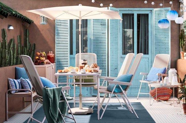 تصویر یک بالکن به رنگ آجری و آبی با میز و صندلی و سایبان