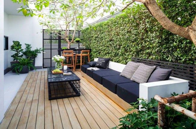 مبلمان مشکی و صندلی های چوبی و دیوار سبز