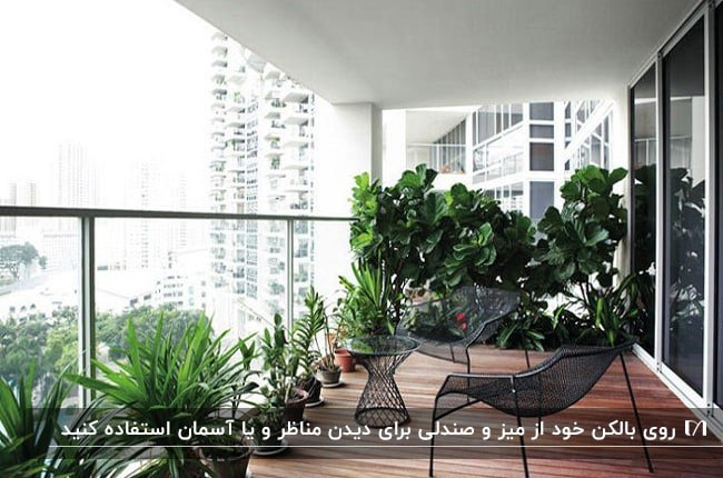 بالکنی بزرگ با کفپوش چوبی، میز و صندلی های فلزی مشکی و گلدان های بزرگ گل