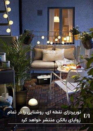 تراس نورپردازی شده ای با میز و صندلی و مبل سفید و گیاهان گلدانی