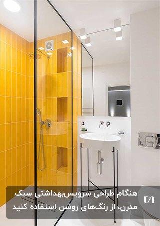 سرویس بهداشتی مدرنی با کاشی های سفید و زرد و پایه لوازم مشکی