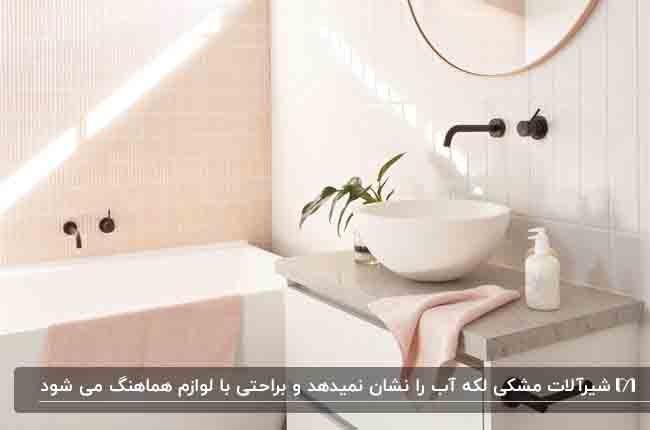 حمامی با کاشی های سفید و صورتی و شیرآلات مشکی مات دیواری