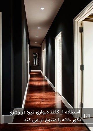 راهروی خانه ای با دیوارهای مشکی، درب سفید و کف چوبی