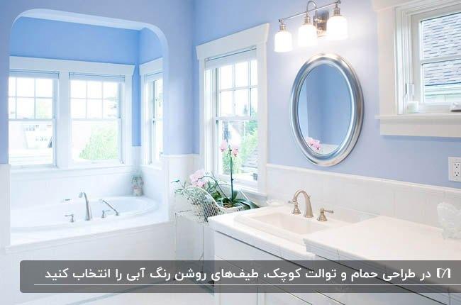 سرویس بهداشتی با دیوار های سفید و آبی، آینه گرد و پنجره های مربعی