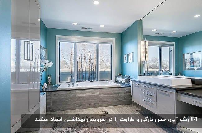 سرویس بهداشتی بزرگی با تم رنگی طوسی و آبی و سقف نورپردازی شده با هالوژن
