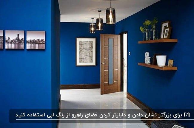 راهروی ورودی خانه ای با دیوار آبی، تابلو و قفسه