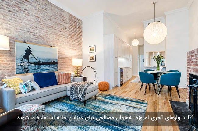 نشیمنی با مبل طوسی، کوسن، تابلو و فرش با زمینه آبی و دیوار آجری