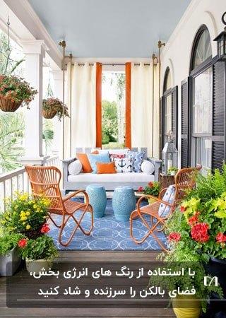 تراس خانه ای با فرش آبی، مبل سفید، صندلی های نارنجی و گلدان های گل سبز