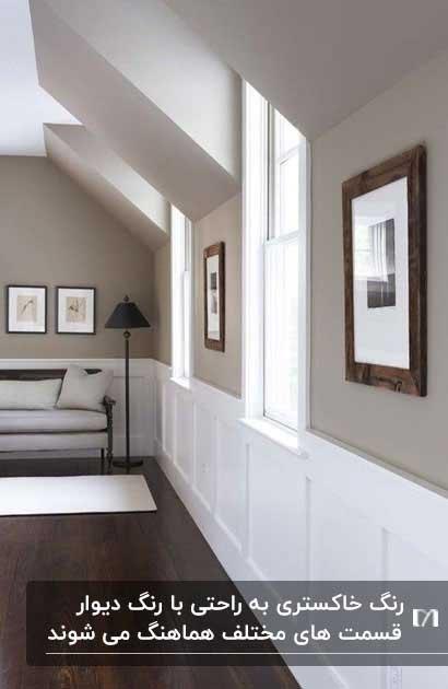 راهروی خانه ای با دیوارهایی به رنگ خاکستری گرم به همراه تابلوهای دیواری