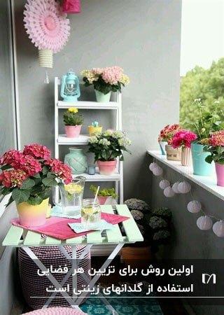 گلدان های تزئینی رنگی برای روی تراس با میز و صندلی سفید