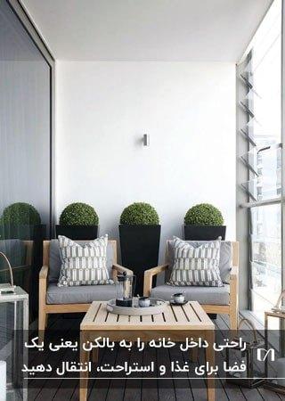 میز و صندلی چوبی با پارچه طوسی روی یک بالکن کوچک برای غذاخوری