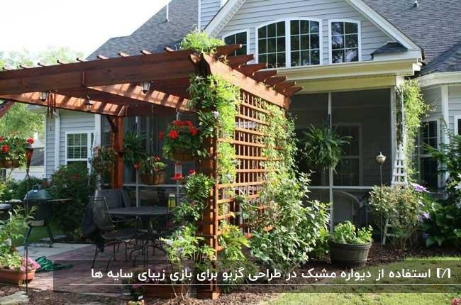 تصویر گزبویی چوبی با دیواره مشبک و گیاهان رونده اطرافش